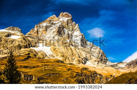 Snow capped mountain peak against the blue sky. Mountain peak snow. Snowy mountain peak view. Mountain rock