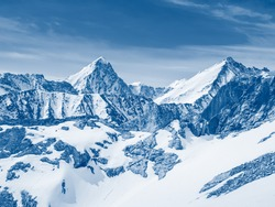 Snow-capped mountain peaks against a bright blue sky. The concept of recreation and adventure.