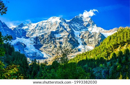 Snow capped mountain peaks rise above the forest. Snowy mountain peaks view. Mountain peak snow