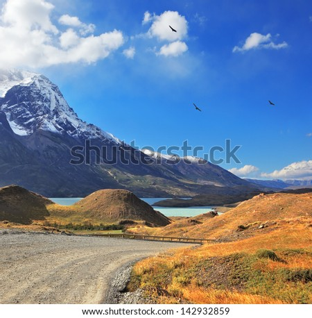 Snow-capped mountain peaks, the lake and the gravel road. Dreamland Patagonia