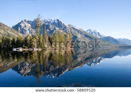 Snow capped mountain reflected in a crystal clear lake - stock photo