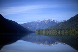 Snow capped mountains, green conifers and blue sky reflecting in Birkenhead lake as in a mirror, on the still water, in a secluded destination of BC, Canada