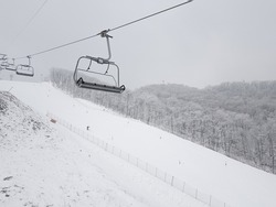 Snow-capped mountains, lifts on ski slopes, numerous skiers and boarders