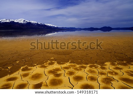 Snow capped mountains reflected in a lake. Alvord Desert, Eastern Oregon, USA/Desert Mountains