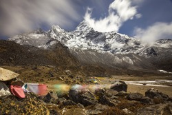 Snow-capped Mt Ama Dablam panorama in the Himalayas. View to Ama Dablam base camp with yellow camps. Long exposure shot, blurred clouds above, blurred prayer flags on the rocks in the foreground.