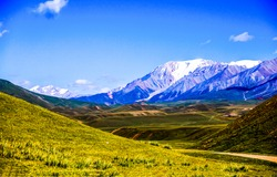 Snow capped peaks over a mountain valley. Mountain valley peaks snow. Mountain valley landscape