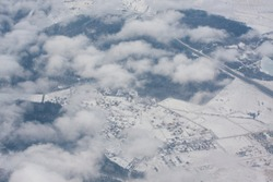 Snow city in clouds. Airplane top view.