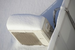 Snow covered Air conditioner outdoor unit closeup on roof top in snowdrift at winter day top view