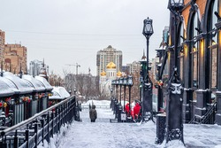 Snow-covered alley with street lights and Gothic-style buildings, in the foreground. Behind it is an Orthodox church with golden domes and buildings under construction
