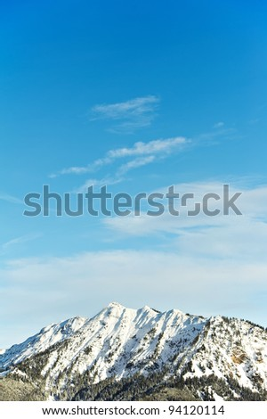 Snow covered beautiful alpine mountain peaks over blue sky