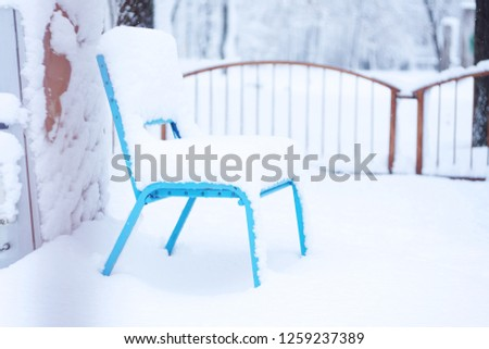 Snow-covered bench in the city amusement park. Forged metal and wooden park bench and trees covered by heavy snow. Winter Outdoor Activities #1259237389