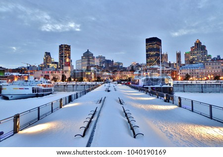Snow-covered benches, pier, waterfront walkway, harbor, and downtown Montreal after sunset in winter - Montreal, Canada