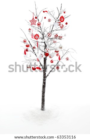Snow covered branches and twigs of a deciduous tree is decorated with red and white Christmas baubles