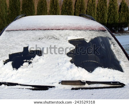 Snow covered car front window partly cleaned both sides, horizontal