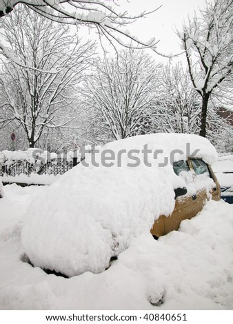 Snow covered car in a winter day