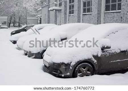 Snow-covered car in the parking lot. Urban scene. After a snowstorm. Clean automobile from the snow.