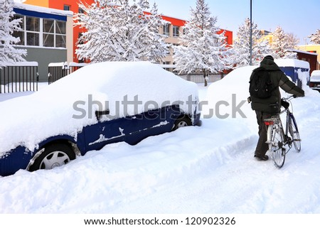 snow-covered car lot in town with cyclist