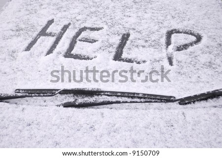 Snow covered car windscreen with the word help written in the snow