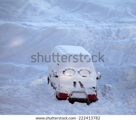 Snow-covered car with smiley in windshield. Ski resort at evening.