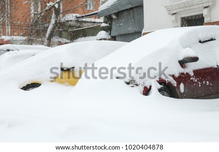 Snow covered cars on a parking near building #1020404878