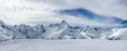 Snow covered Caucasus mountains with Mt. Belalakaya at winter cloudy day. Panoramic view from Mt. Mussa-Achitara slope, Karachai-Cherkess, Russia.
