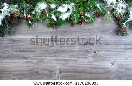 Snow covered Christmas tree evergreen branches placed on top of a rustic wooden background   #1170186085