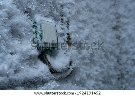 Snow covered device with switch on frozen wall in winter Foto d'archivio ©