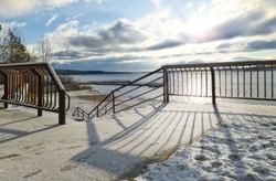 Snow-covered fence and descent to the beach on the winter embankment in the morning