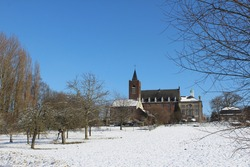 Snow covered Flemish landscape looking accross to the abbey of Affligem, in Flemish Brabant, Belgium. With copyspace top left