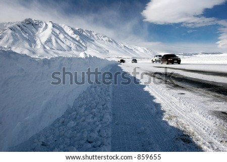 A neve cobriu a estrada no inverno com os carros que passamperto e as montanhas na distância