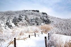 Snow covered hiking trail with hoarfrost on the tree against Ipseokdae Rock of Mudeungsan Mountain at Dong-gu near Gwangju, South Korea