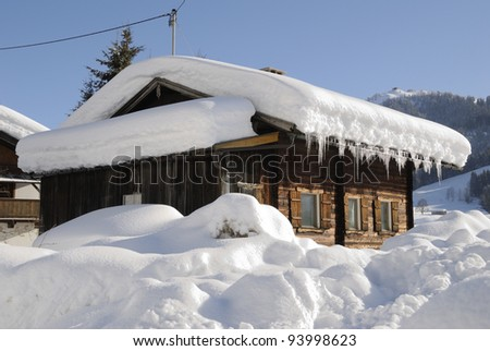 Snow covered house in austrian winter landscape - stock photo