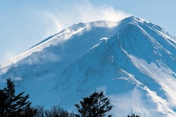 Snow covered icy peak of Mount Fuji. Japan's highest mountain and active volcano. Winds blowing snow from the mountain peak.