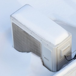 Snow covered invertor Air conditioner outdoor unit close up on roof top in snowdrift at winter day top view closeup