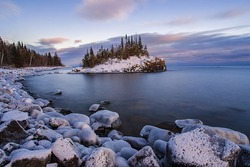 Snow covered island on Lake Superior during sunset.