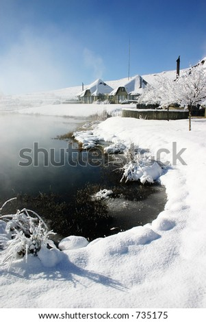 Snow covered lakeside holiday homes