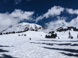 Snow-covered Mount Rainier looms over snow-filled basins on a blue spring day