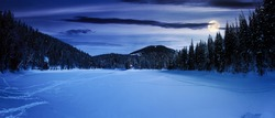 snow covered mountain lake at night. green spruce trees on the shore in full moon light. clouds on the sky