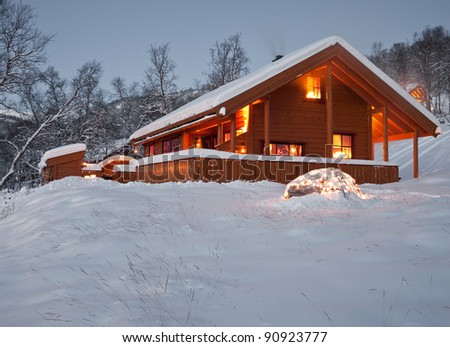 Snow covered norwegian mountain cottage during twilight hours with decoration lights in the foreground at christmas
