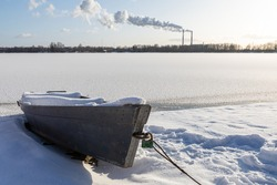 Snow-covered old wooden rowing boat on the shore in winter season. Fishing boat. A frozen lake or river. Low ambient temperature. The season of winter fishing. Sunny winter day.