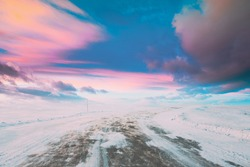 Snow-covered Open Slippy Road During A Snowstorm Blizzard In Winter. Altered Colorful Sunset Sunrise Sky. Dangerous Motion. Strong Wind In Winter Sunny Day. Dangerous Weather Conditions Blizzard In