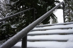 Snow-covered outdoor stairs and frozen railing after snow and freezing rain in the winter.