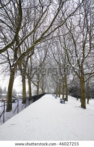 Snow-covered park with trees and benches in England.