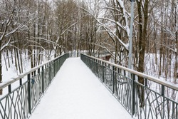 Snow-covered, pedestrian bridge over a ravine in the winter forest. Lots of snow on a beautiful road towards the forest.