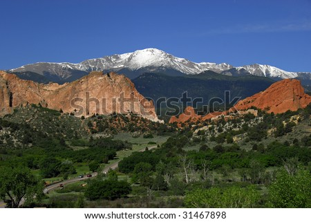 Snow covered Pikes Peak at the Garden of the Gods Park near Colorado Springs, Colorado with two automobiles dwarfed by the spacious landscape