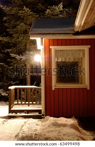 Snow-covered porch of the house and night lantern
