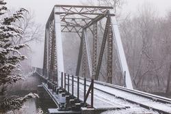 Snow covered railroad bridge on a foggy winter morning