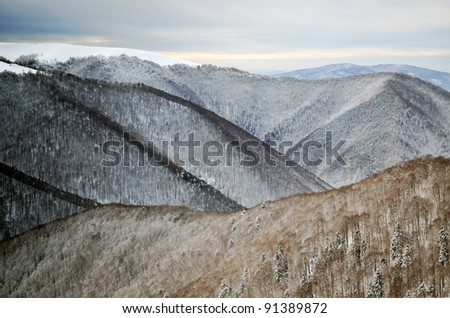 Snow covered ridges in winter mountains - stock photo
