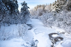 Snow covered river in a Wisconsin forest in January with blue skies, horizontal