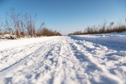 Snow covered road. Grass in the snow.